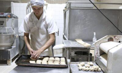 Padeiro produz pequenos pães na cozinha da padaria (matéria sobre MEI)