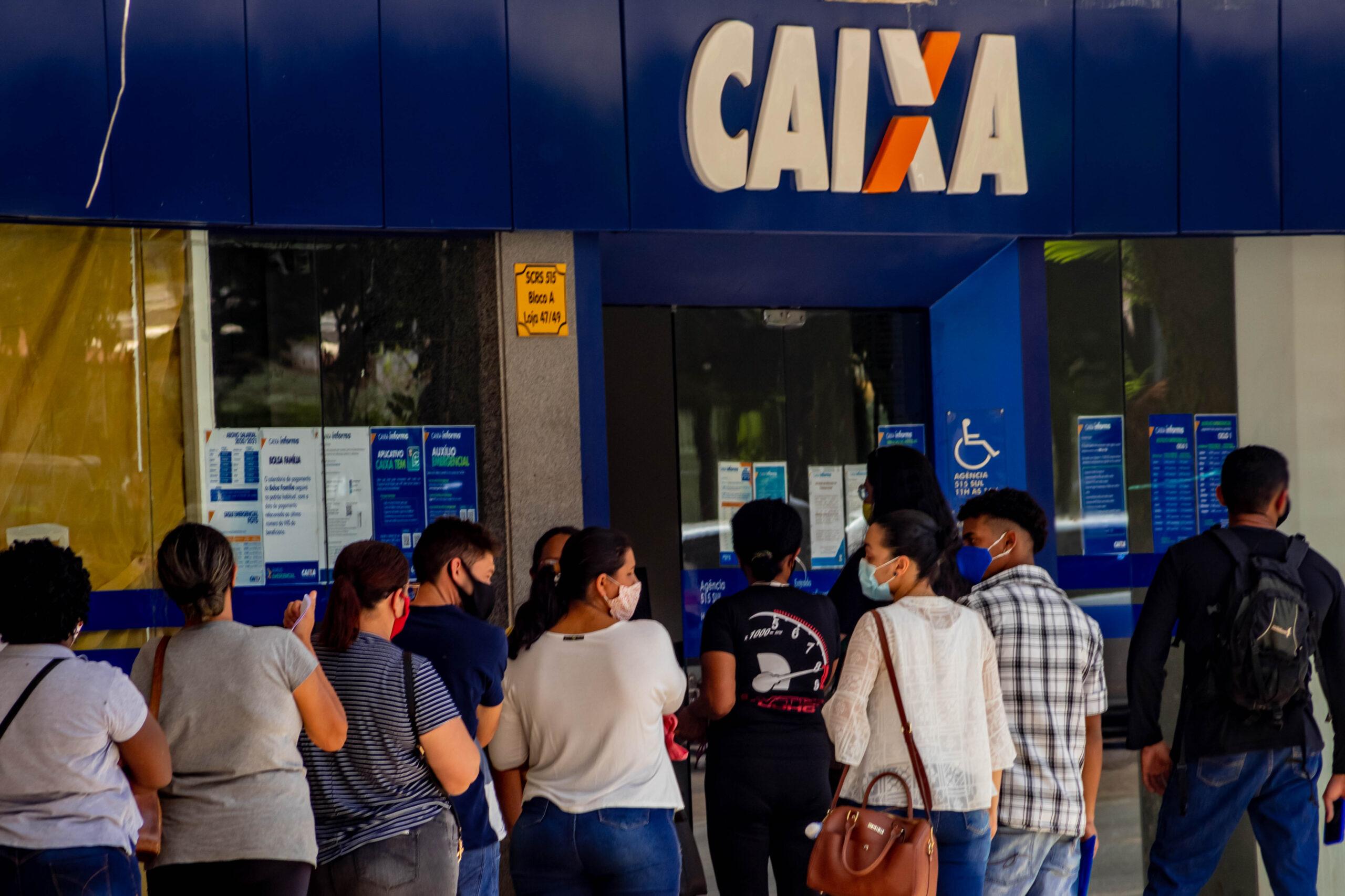 Fila de pessoas em frente ao banco da Caixa Econômica Federal ilustrando quem vai ao banco para resolver detalhes do auxílio emergencial