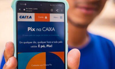 Segurando o celular com o aplicativo da caixa aberto na pagina do Pix