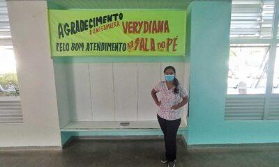 Paciente em frente faixa em homenagem à enfermeira